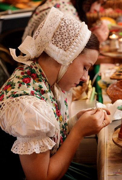 Ethnic Sorbian Melanie Baier, wearing a traditional Upper Lusatian folk dress and white headdress, paints Easter eggs in traditional Sorbian motives at the annual Easter egg market on March 21, 2010 in Schleife, Germany.