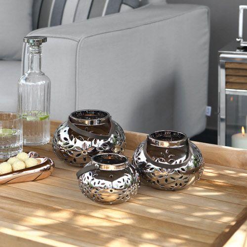 FInk Laterne LILLY -  Laterne aus Porzellan, silberfarben, erhältlich in 3 verschiedenen Größen  Die hochwertige Laterne LILLY aus dem Hause Fink zaubert duch die dekorativen Ausstanzungen stimmungsvolle Lichteffekte. Sie ist auch bei Tag ein stilvoller Blickfang. Der Henkel ist aus Lederoptik.
