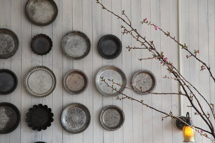Don't limit yourself to plates, vintage pie tins in varying shades of steely grey looks great too.