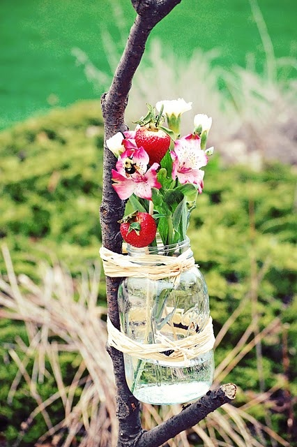 I love these vases- mason jars tied on to a stick.