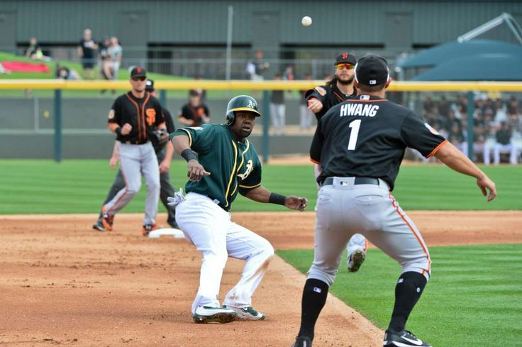 Nowhere to run:    Oakland Athletics center fielder Alejandro De Aza is run down by San Francisco Giants third baseman Jae‐Gyun Hwang and shortstop  Brandon Crawford during the first inning at HoHoKam Stadium in Mesa, Ariz. Oakland won 6‐1.