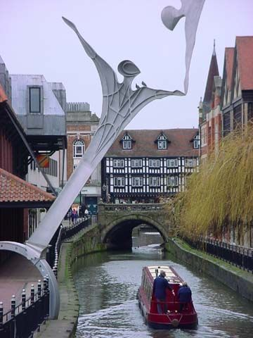 "The canal running through downhill Lincoln underneath the High Bridge, with the ""Empowerment"" sculpture in the foreground. Lincoln has a huge turbomachinery plant, currently run by Siemens, and the town has a long association with gas turbines."