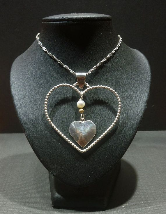 A gorgeous heart shaped pendant adorned with a small silver heart. The silver heart is set off by a lovely cultured freshwater pearl and a gold