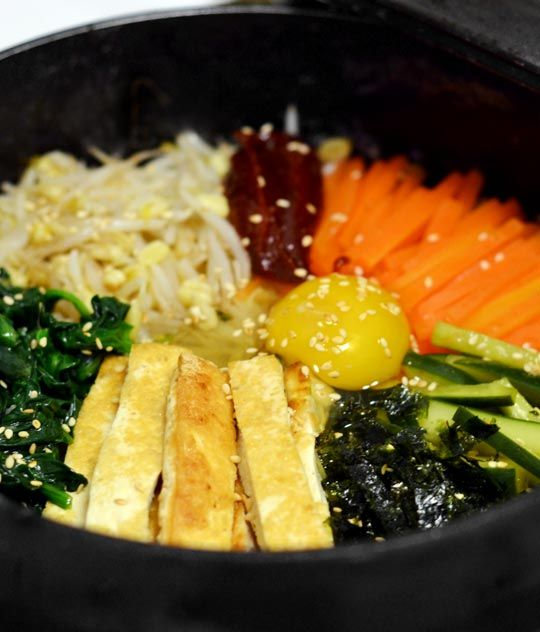 "In Korean, bibimbap means ""mixed rice"" – a dish composed of cooked rice and an assortment of vegetables (and often meat or tofu and an egg), all stirred together with a dollop of hot red pepper paste just before eating. It's a flavorsome and remarkably healthful medley of colors, textures, and flavors."