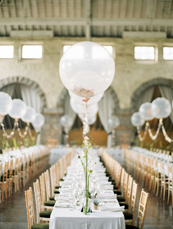 If a shiny mylar balloon sign seems a little too eccentric for your style, simple balloon centerpieces are fit for a more traditional wedding. Lined with garlands of flags, these balloon centerpieces look super elegant on long tables.