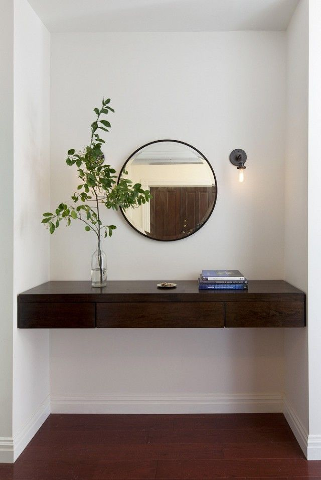 Hallway with floating wood shelf, an indoor plant. and a mirror