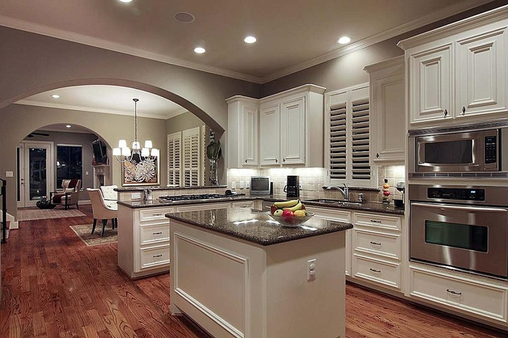 White cabinets, travertine backsplash, hardwood floors, and stainless