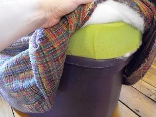 diy storage ottoman. regular plastic storage tub turned into ottoman. hmm.