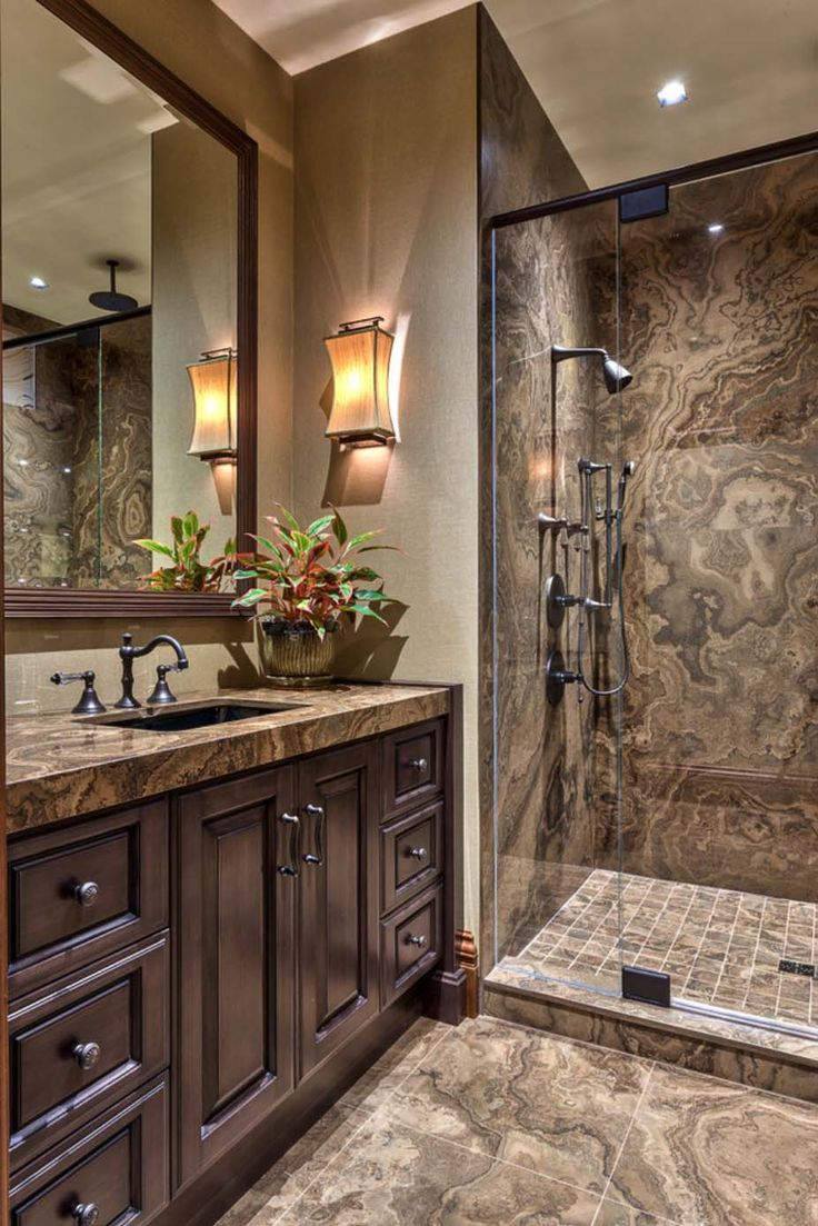 "In the mountains of North Carolina is this eye-catching mountain resort bathroom. Features include custom designed cabinetry in a a grey wood stain with charcoal glaze; Magic Brown granite in the shower; and this wall finish is actually a wallcovering, however the designer suggests a great substation if you wish to emulate this look: Benjamin Moore ""Revere Pewter"" HC-172."