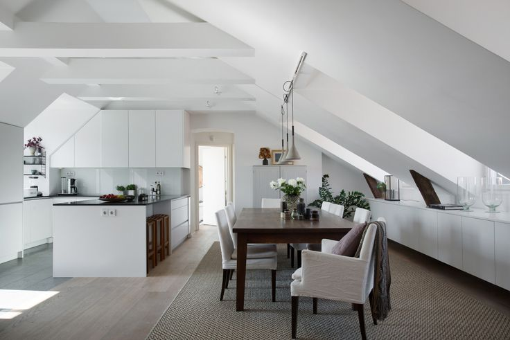 Kitchen and dining space with slanted ceilings in a Stockholm penthouse