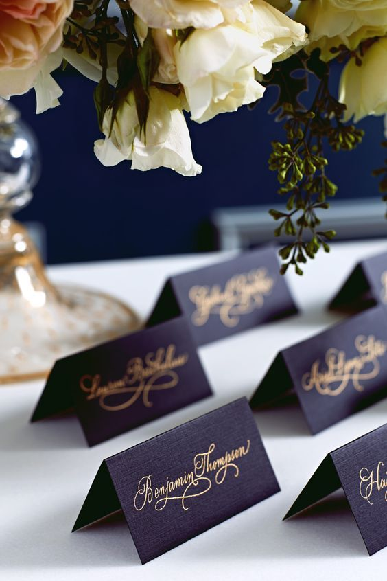 splendid feast with navy place cards adorned with golden scrip / http://www.deerpearlflowers.com/navy-blue-and-gold-wedding-color-ideas/
