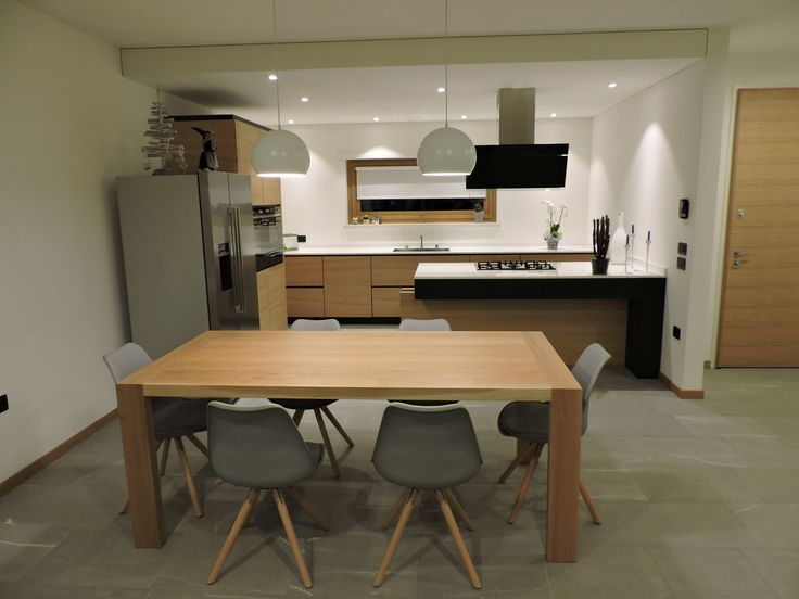 Cucina dalla linea minimal in rovere bicolore effetto segato con maniglie a scomparsa e penisola dalla linea pulita e particolare. Piano in Okite.