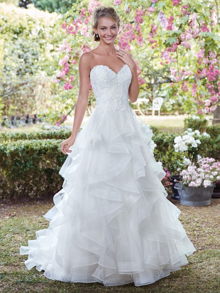 Rebecca Ingram - GRACE, This gorgeous A-line wedding dress features swirling layers of tiered tulle with horsehair. A strapless sweetheart neckline completes the bodice, featuring swirls of beaded lace appliqués. Finished with covered buttons over zipper and inner elastic closure.