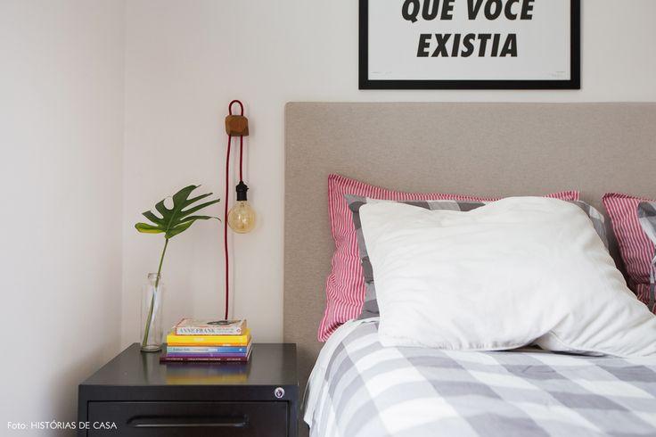 Quarto de casal tem roupa de cama xadrez, cabeceira revestida com tecido e armário metálico como criado mudo.