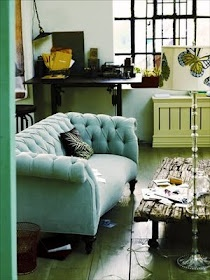Bohemian Vintage by Anthropologie. Tufted light turquoise sofa. Rustic coffee table. Eclectic living room.