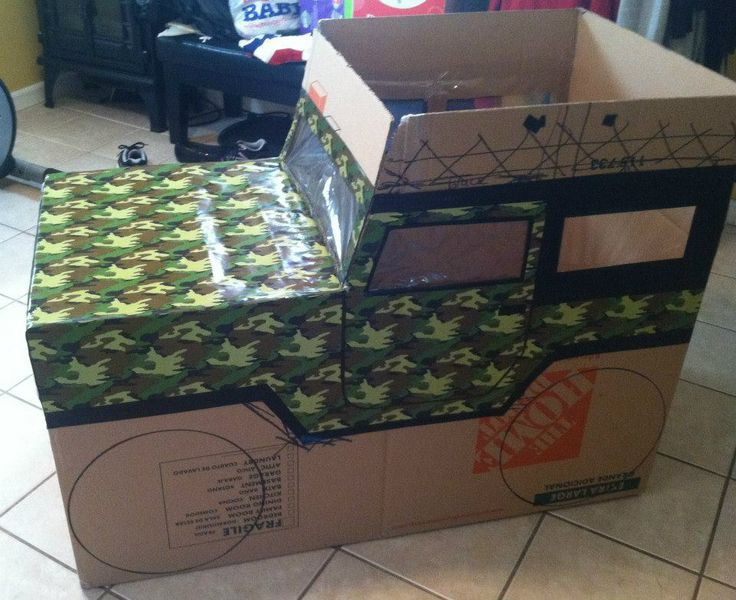 Step 2:  After I sketched a basic outline of the Jeep, I used camo wrapping paper that I found at Party City for the body of the Jeep and sliced open ziploc bags and glued them into the inside of the truck for the windows and windshield.  I used black electrical tape and black marker for the trim and to outline the doors.