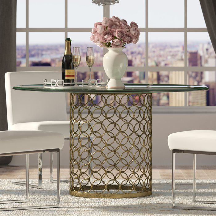 This glamorous table features a glass top and golden base, making it the perfect piece for any fashionista's kitchen or dining room. Top it with gilded accents and pillar candles for a refined vignette, or pair it with neutral-hued side chairs and classic white porcelain plates for an elegant aesthetic.