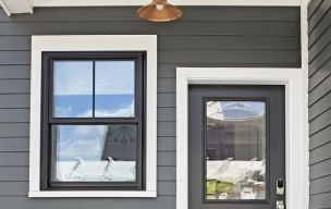 Triple-pane vinyl windows combine a classic 2-over-1 farmhouse look with top performance and durability. With Krypton-gas in the air spaces and a low-E coating, they carry a 0.17 U-factor, which indicates a low rate of nonsolar heat transfer. They are key to the house's Home Energy Rating score of 55, which indicates it will average 45 percent of the energy use of a typical house of similar size. Harvey Building Products