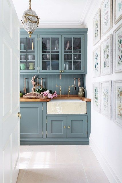 'Anyone can pick a paint colour, but getting the structure right is what makes a house', says Amanda Hornby, the interior designer who tranformed this Cotswolds dovecote into a family home. Amanda designed the cupboards in the kitchen, painted in Farrow & Ball's 'Card Room Green'. The green tone of the cupboards adds a fresh feel to the room, complimented by the green tones in the artwork on the gallery wall. Brass taps and fixtures give a feel of elegance to the simple style of the space.