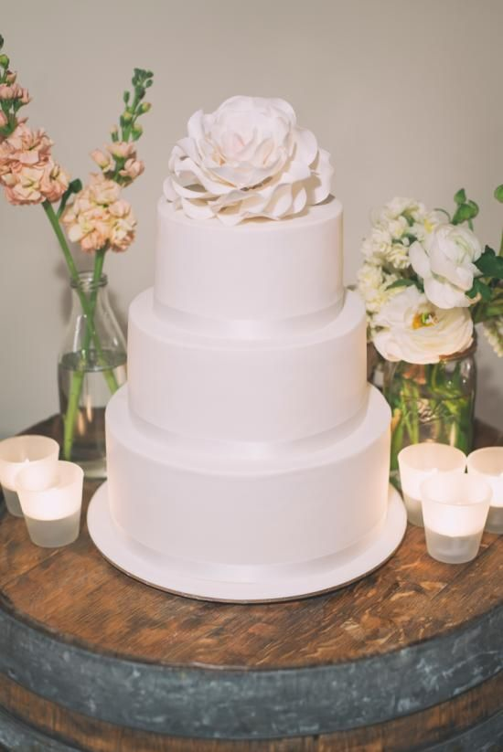 Beautiful Wedding Cake set on a wine barrel with frosted glass tealight candles with @simplyperfect and @richbayleyphoto