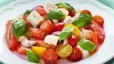 TOMATENSALADE MET MOZZARELLA 4 tros tomaten en 250 gr cherrytomaatjes, gele tomaatjes en/of snacktomaatjes in partjes, 1 ui in dunne ringen, 2 bollen mozzarella uit laten lekken en in blokjes snijden, 2 eetl olijfolie, 1 eetl witte wijnazijn,  snufje peper en zout, schep alles voorzichtig door elkaar en bovenop blaadjes basilicum.