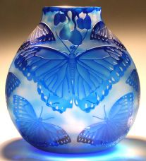 Heron Glass, Blue Morpho: by Mary Mullaney  who with her husband Ralph Mossman are known by their peers and fellow glass artists as a skilled and agile team in the field of glassblowing. As a husband/wife duo collaborating as equal partners in the production of each piece, they are unique in the way they move and work together to create their contemporary glass.
