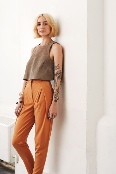 Cropped brown sleeveless shell top over very high waisted, fitted, and pleated orange trousers. Love the colours and the silhouette.
