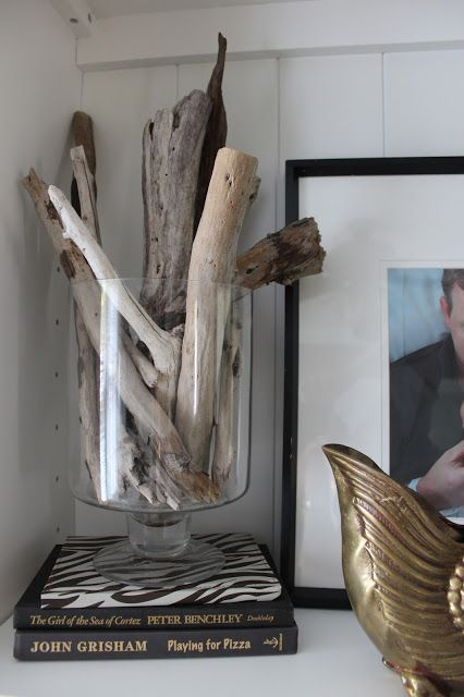 Love the simplicity of found pieces of driftwood displayed in a glass hurricane!