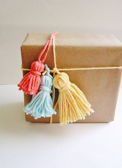 Colorful tassels add a fun touch to this brown paper package #etsypackaging