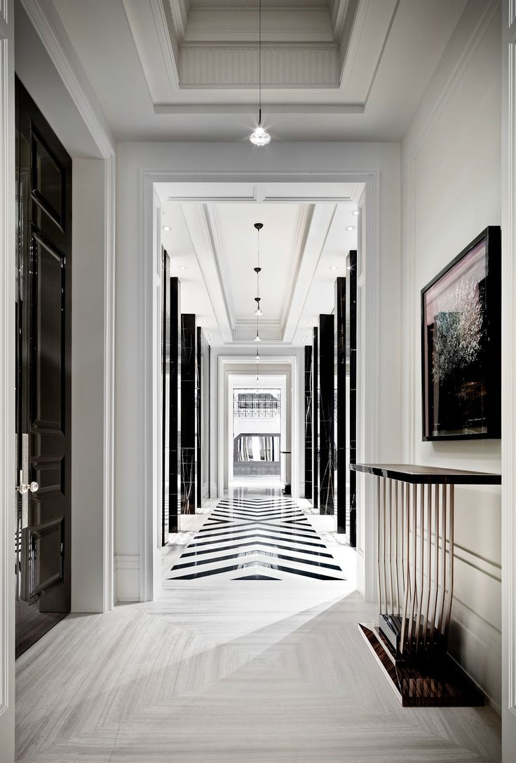 A hallway highlights the black-and-white palette with a chevron tiling pattern and marble-clad columns.