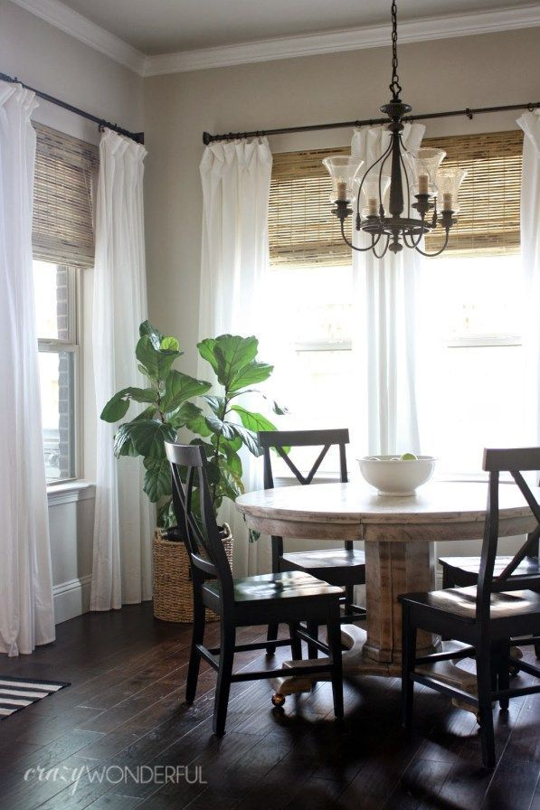 Dining room with cream curtains and bamboo blinds.
