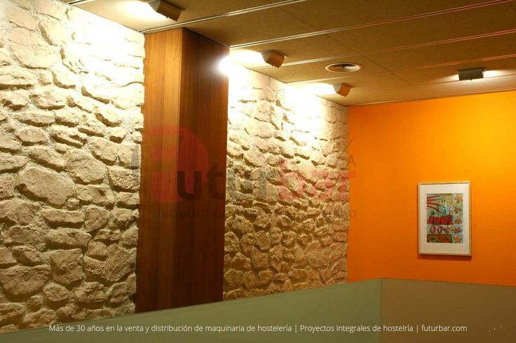 Paredes con diseño en piedra y elementos revestidos en madera. Realización de ambientes por futurbar.com