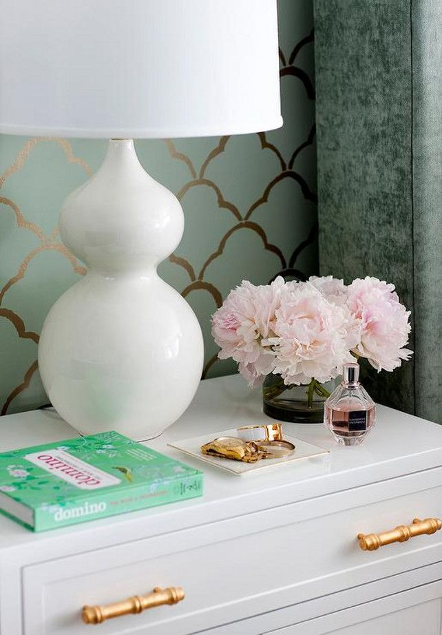 Bedroom. Grey bedroom features an accent wall clad in green and gold scallops wallpaper lined with a white nightstand with gold bamboo pulls, Worlds Away Marcus White & Gold Leaf Cabinet, topped with a white glass lamp.  JWS Interiors.