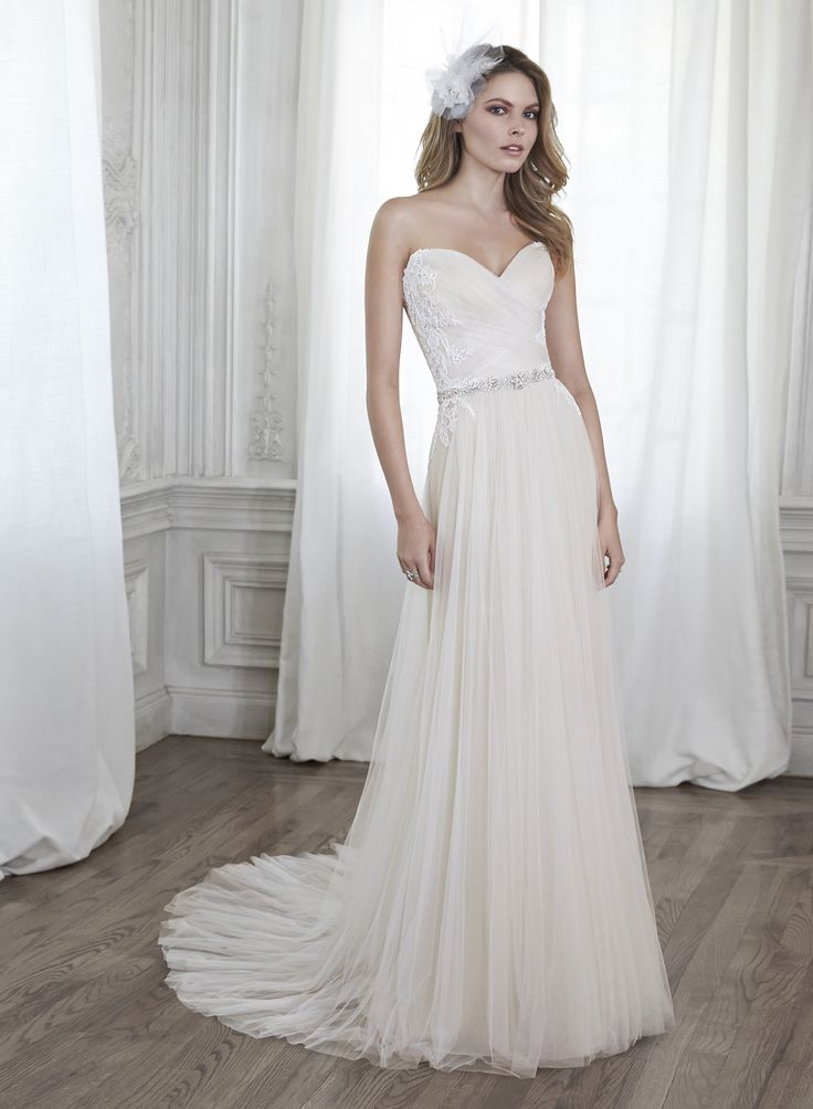 Patience - by Maggie Sottero  This stunning tulle sheath gown is accented with dainty lace appliqués on the bodice and a delicate Swarovski crystal waist. Finished with sweetheart neckline and corset back closure