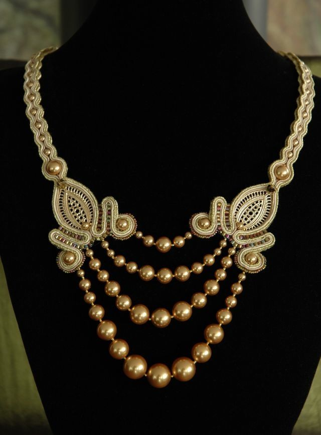 Sutasz w kolorach: złoto, ecru, Swarovski - perły, Swarovski - kryształy, Miyuki Beads, elementy ze srebra pokrytego 24k złotem, elementy metalowe w kolorze złotym, rewers zabezpieczony jagnięcą skórą w kolorze złotym.