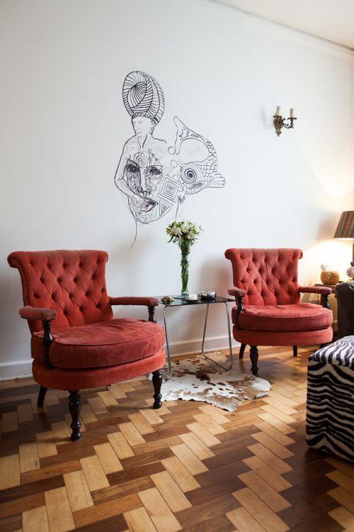 Obra de arte desenhada na parede entre duas poltronas de veludo vermelho. / Artwork drawn on the wall between two red velvet armchairs. (Casa de Rodrigo Pitta, artista multimídia)