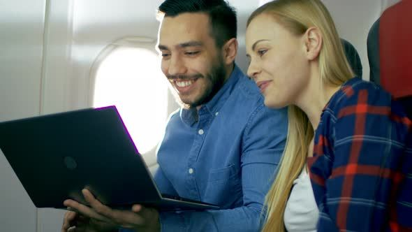 On a Plane Beautiful Young Blonde with Handsome Hispanic Male Watch Movies on a Laptop