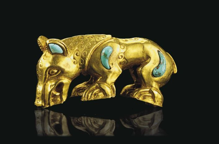 Scythian art gold zoomorphic handle, Southern Urals, 4th century B.C.  Formed of sheet, in two halves, hammered over a wooden mold and chased, in the form of a predator, perhaps a wolf, standing four-square, its head down, baring fangs, with drop-shaped turquoise inlays on the shoulders and haunches, the interior of the ears also inlaid in turquoise, the bottoms of the feet and mouth once conforming to the curvature of a vessel wall, originally set vertically, 7.3 cm long. Private collection