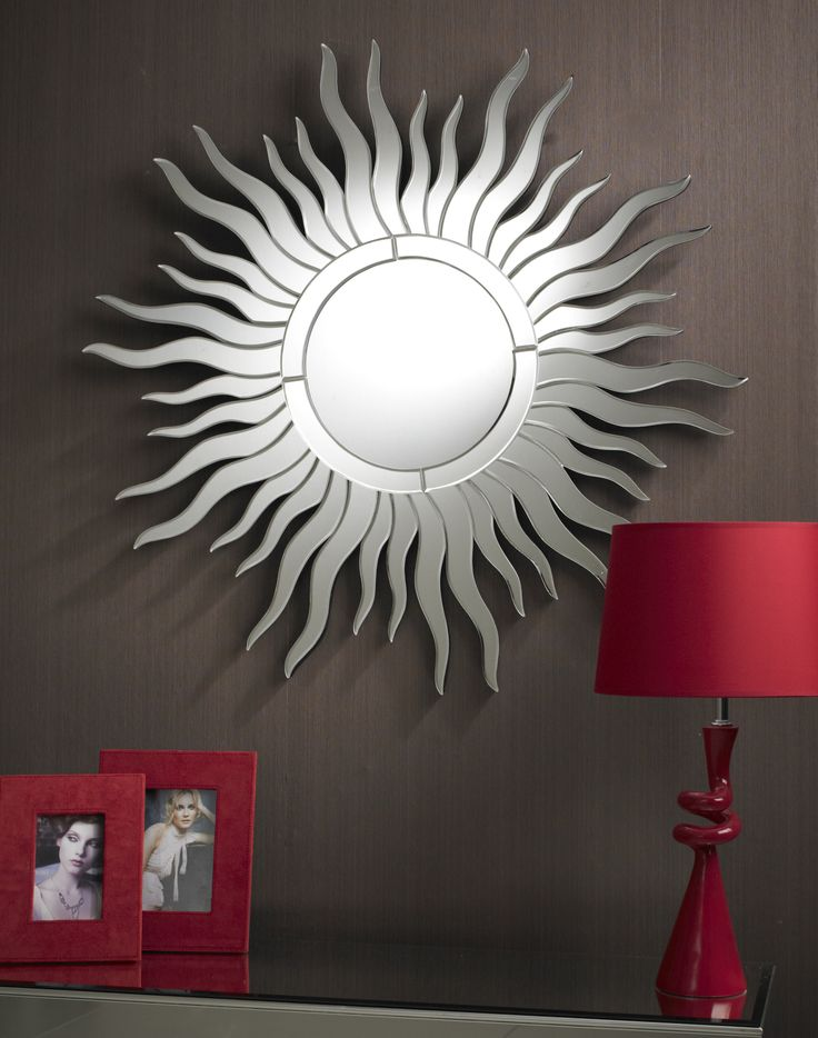 The Sun Ray Mirror is something of a classic in Art Deco styling; there is a clear glass circular centre with a slim border split into 4 parts. Around this are many suns wavy rays of 2 different lengths, set out in pairs. This all comes together to make a terrific iconic sun design.