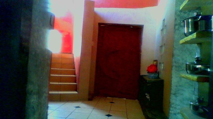 The entrance Door of the livingroom next to the staircase with red wall leading to the back of the cement room diving unit,  temporarily with kitchen pots after passing the previous green and black fireplace behind the door.