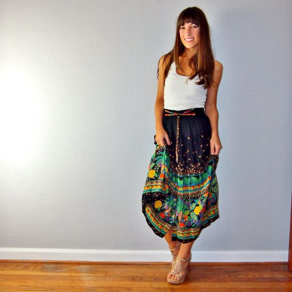 This darling skirt will whisk you away to the tropics. Elastic waist band and buttons down the front, with a unique colorful accent tie on the waist.Very flattering cut with the most beautiful sway when you walk. In excellent vintage condition!