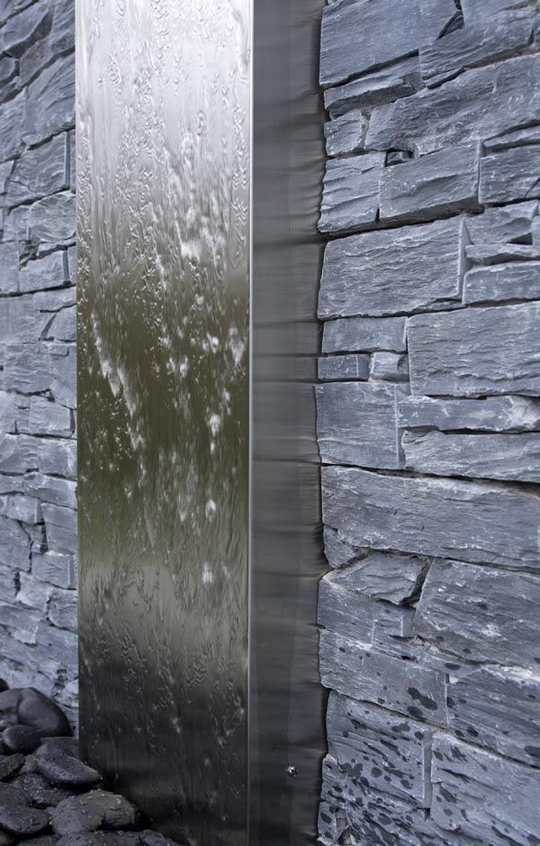 Stainless Steel Water Feature set within dry stone wall and black pebbles at the base.