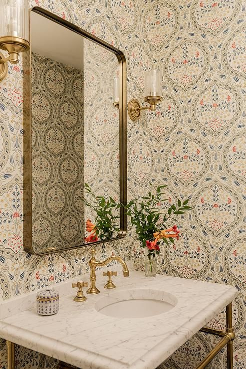 Clad in gray and blue medallion print wallpaper, this small powder room features a Restoration Hardware Bristol Flat Mirror mounted between glass and brass uplight sconces above a marble top brass washstand fitted with a round sink and an antique brass faucet kit.