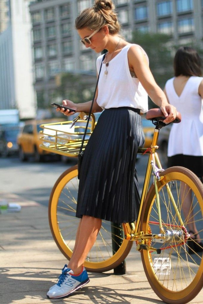 white tank top, black pleated midi skirt, white and blue low top sneakers, black leather shoulder bag