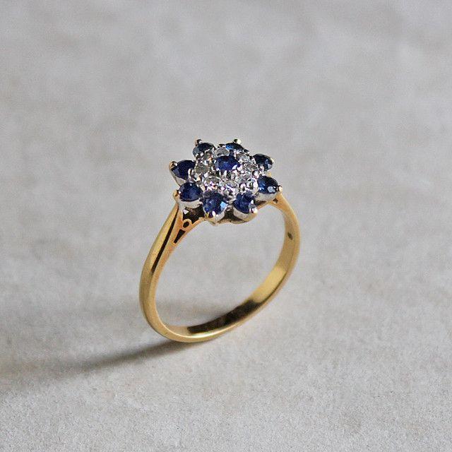 イギリスから入荷した、クラシカルなヴィンテージ・サファイア&ダイヤモンドリング。 美しく輝く9粒のダークブルーのサファイアと、8粒のダイヤモンドが、お花のように並べられたロマンティックなデザイン。リング部分は18金ゴールドで、しっかりとした太さがあり、横から見ると美しい装飾がわかります。*経年による使用感がございますが、ヴィンテージ品につきご了承下さい。