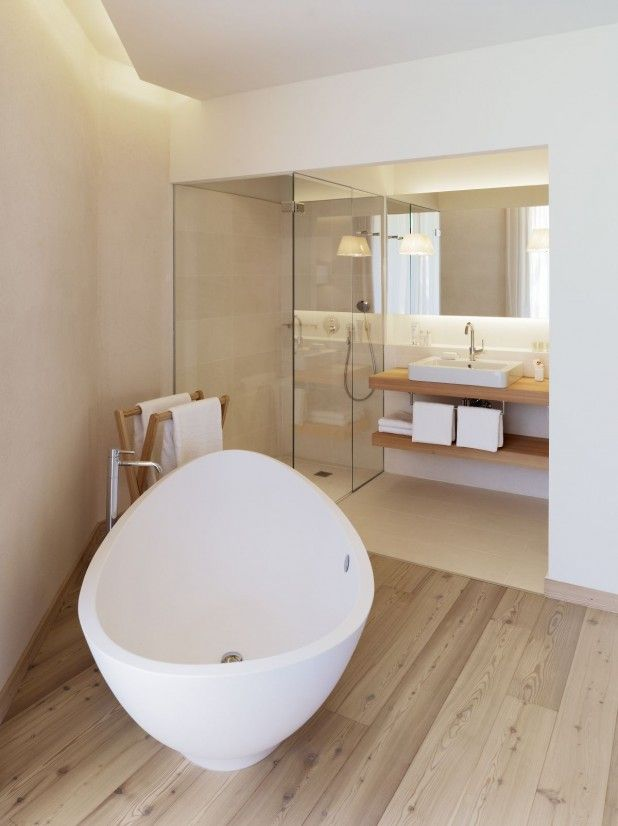 Agreable small bathroom design ideas with white soaking bathtub and floor mounted bathroom watfall bathtub and white vessel sink on wooden vanity also wooden floor bathroom towel holder and glass shower enclosure.