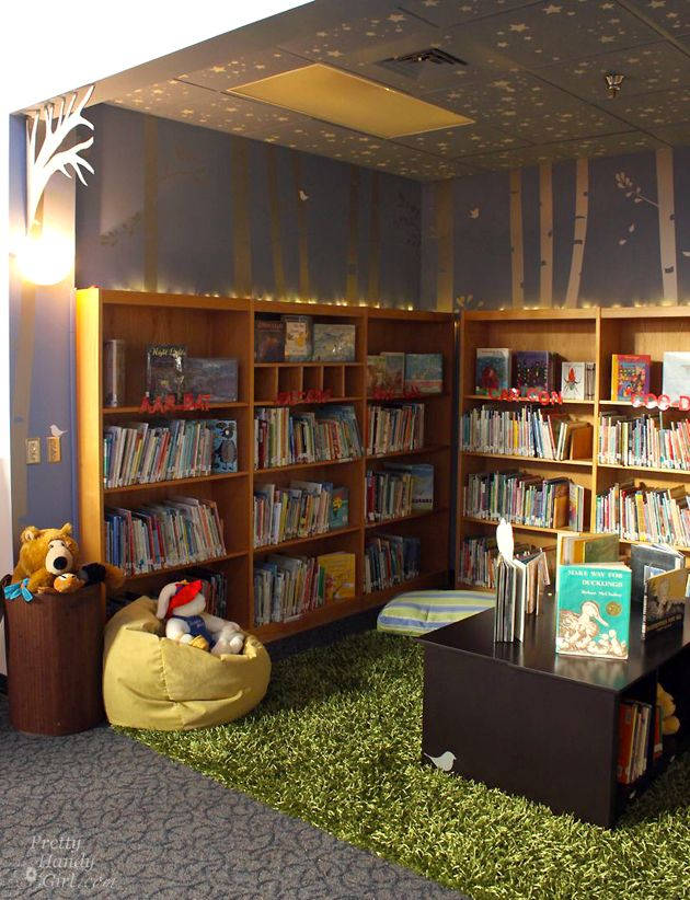 School Library Reveal   Pretty Handy Girl - Mrs. J's Notes: I ADORE the string lights above the bookcases and the wall sconce light instead of the flourescents. Also, the green carpet looks like grass and makes the space so natural looking. Ceiling tiles are painted too with silvers stars!
