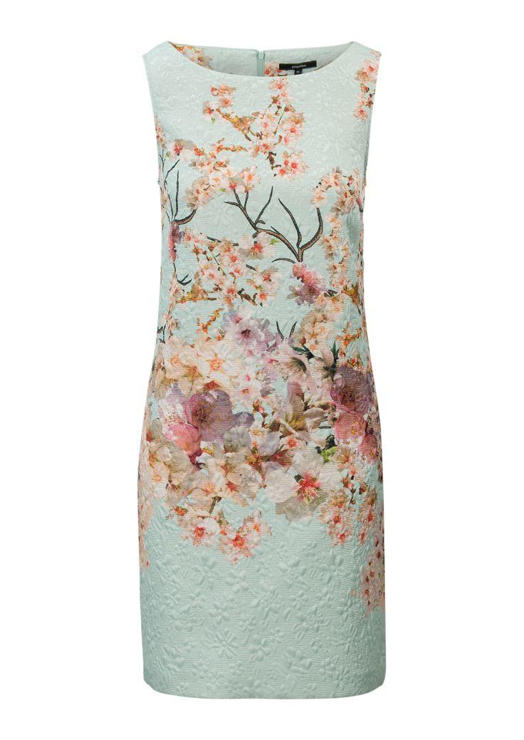 Mintgroene jurk met gekleurd bloemendessin. Voorzien van een tone-in-tone structuurtje. Het is een mouwloze jurk in aansluitend model. Het item heeft een hoge ronde hals. Sluit met een blinde rits aan de achterkant. Lengte tot op de knie.     Let op: de kleur van de jurk wijkt af van de foto en is in het echt mintgroen.