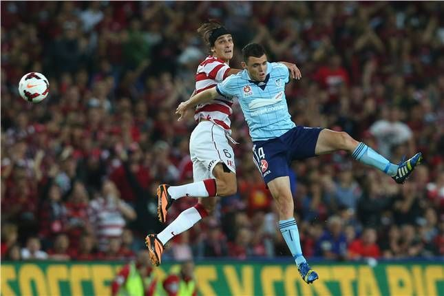 Sydney FC's Mitchell Malia leaps high with Western Sydney Wanderers' Jerome Polenz in the first derby match of the season at a sold-out Allianz Stadium.
