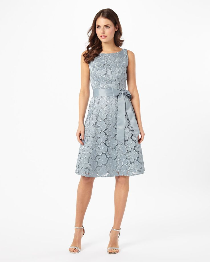 A beautiful fit and flare dress in an open lace design. The dress features a boat neck, removable grosgrain waist tie and tulle under skirt for a fuller shape. Complete with a centre back zip and full lining.